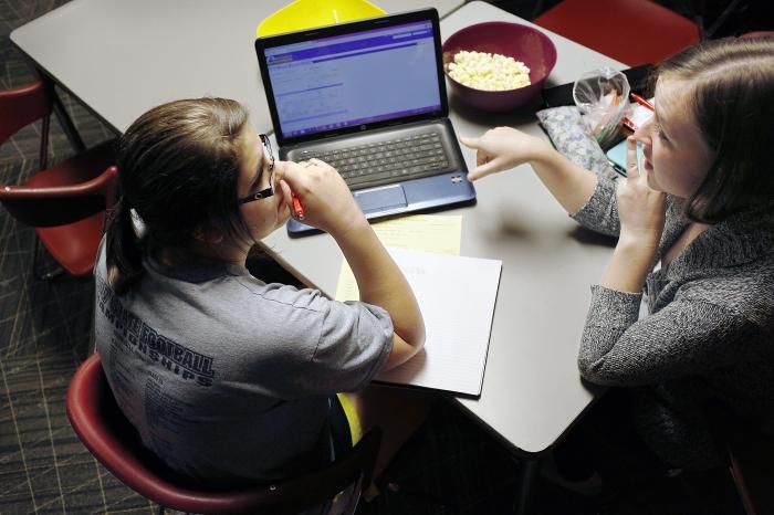 Deux étudiantes installées à une table, devant un ordinateur portable et un bol de popcorn (© AP Images)
