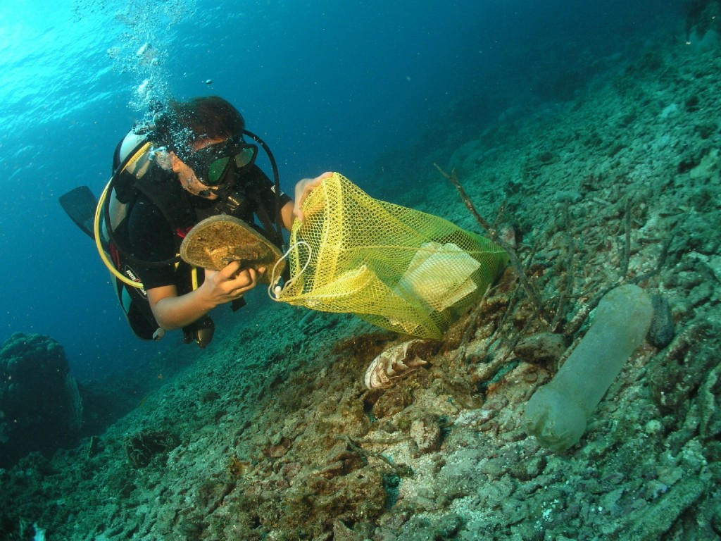 Diver placing debris from ocean floor in bag (Courtesy of Project AWARE)
