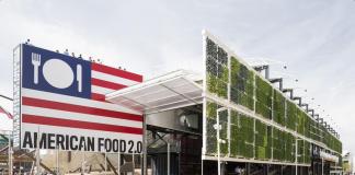 Une foule de personnes entrent dans un stand d'exposition avec une façade végétale et un grand poster du drapeau américain dont les étoiles ont été remplacées par une assiette, un couteau et une fourchette. (ArchiloversCom/Twitter)