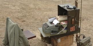Un téléscripteur, un transmetteur et des fournitures de bureau dans une vielle malle ouverte, perchée sur une caisse dans un champ, à côté d'une chaise pliante sur laquelle est posée une veste kaki (Thinkstock)