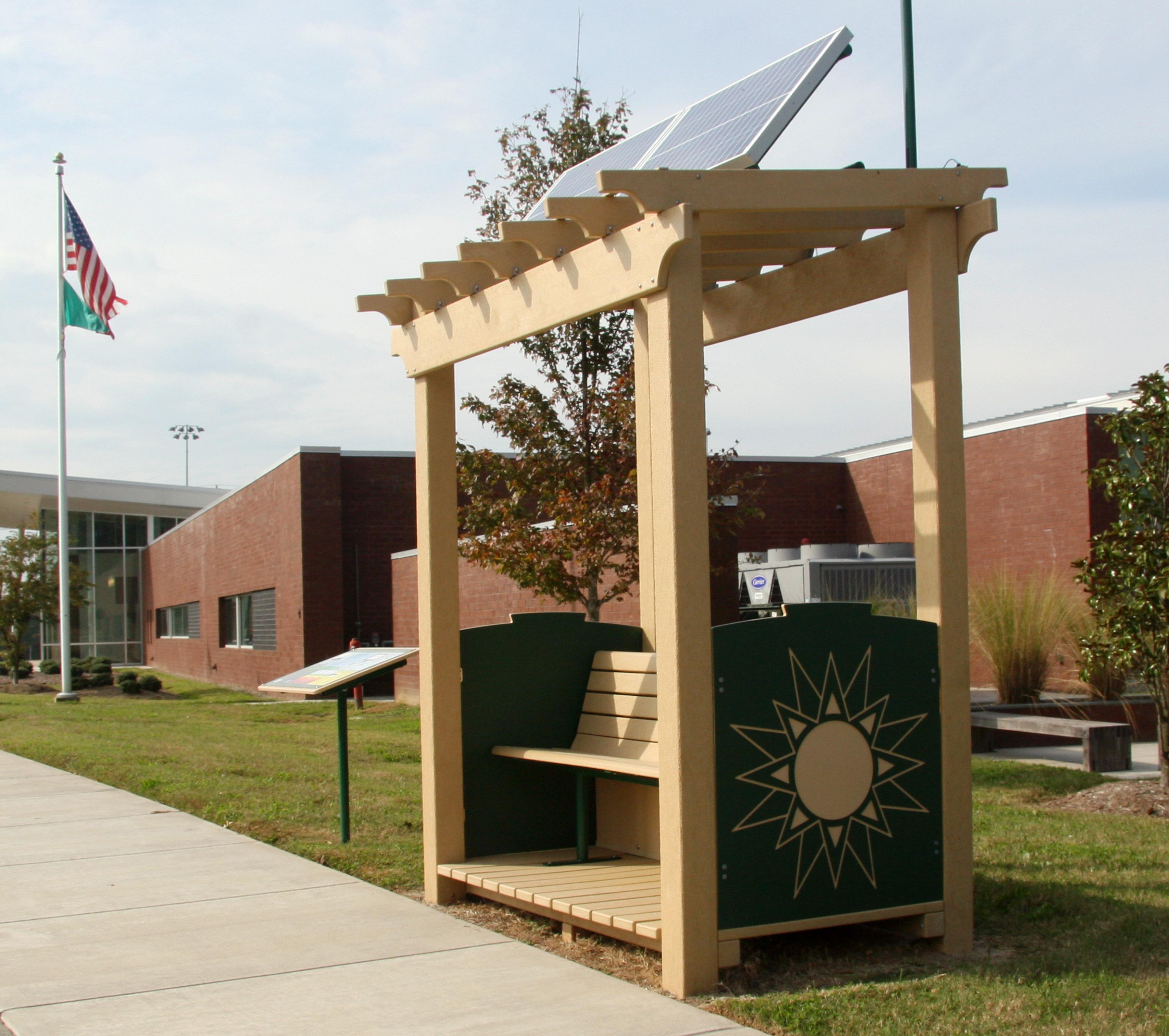 Sur une pelouse devant un bâtiment, un banc couvert surmonté de panneaux solaires, avec un équipement électronique monté sur le côté (EPA)