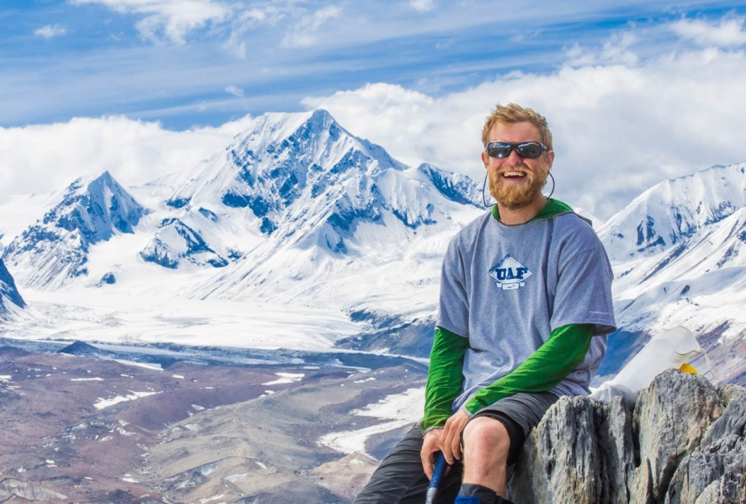 Un jeune homme barbu, le sourire aux lèvres et portant des lunettes de soleil, pose devant une montagne enneigée. (UAF/Todd Paris)