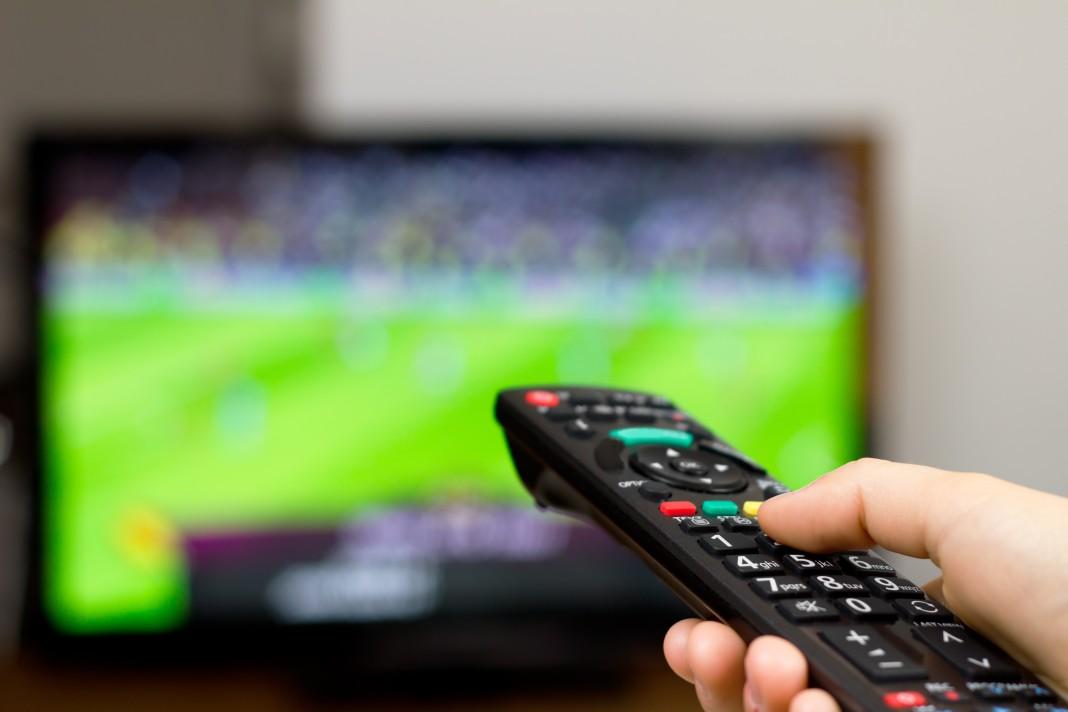 Mano sosteniendo un control remoto de televisión (Shutterstock)