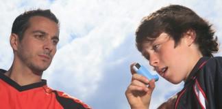Un garçon en train d'utiliser un inhalateur sous le regard attentif d'un homme (Shutterstock/Lopolo)