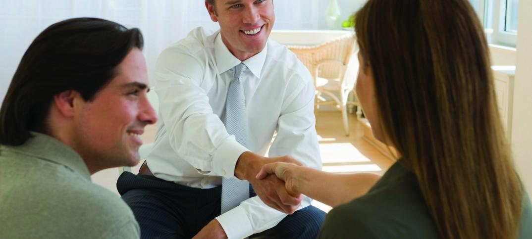 Dos personas estrechándose la mano, otra mirando (Shutterstock)
