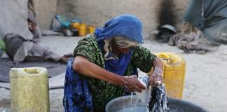 Mujer lavando ropa en un cubo (© AP Images)