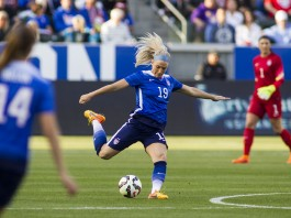 Mujer con uniforme azul a punto de patear un balón de fútbol (© AP Images)