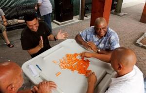 Des hommes assis à une table rient, parlent et jouent aux dominos (Département d'État/Amanda Brown)