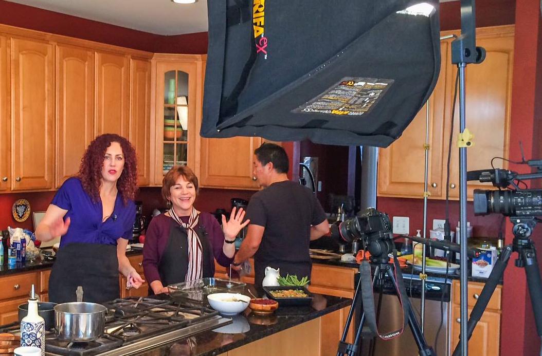 Deux femmes et un homme préparant un repas dans une cuisine pendant qu'on les filme. (Voice of America)