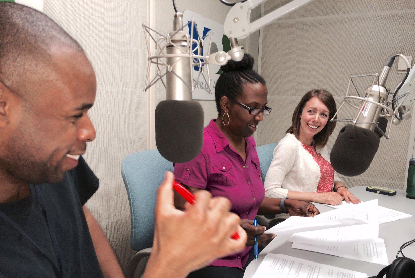 Deux femmes et un homme assis à une table, devant des micros, et révisant des papiers (Voice of America)
