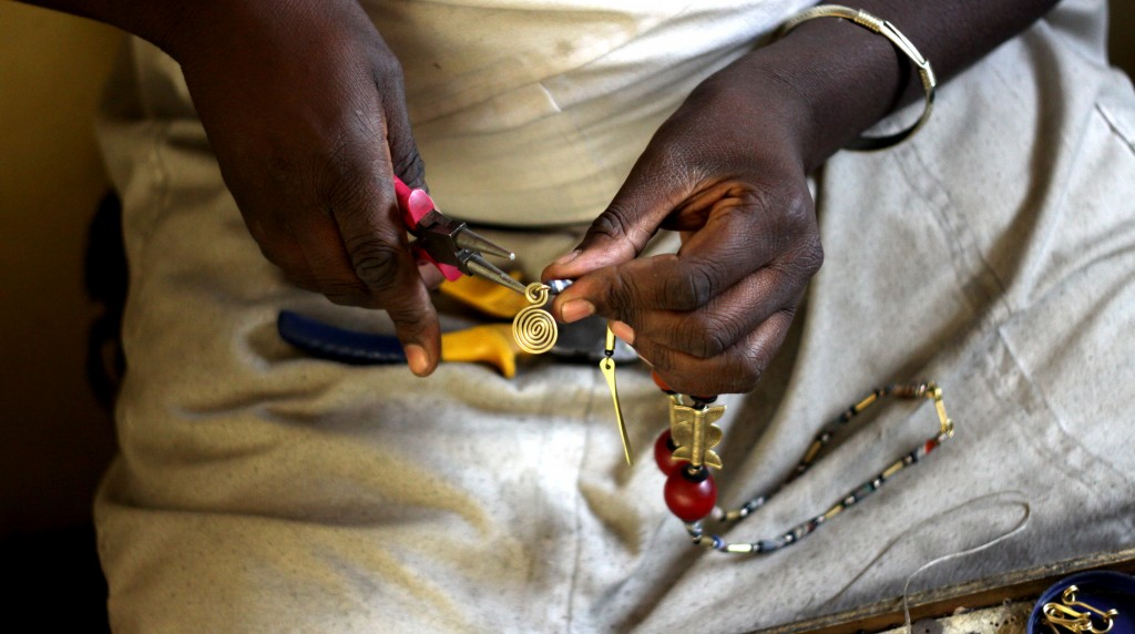 Gros-plan des mains d'une femme en train de fabriquer un bijou avec des pincettes (Crédit photo : Soko)
