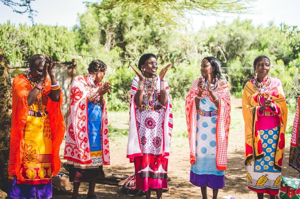 Cinq femmes Maasai en tenues traditionnelles colorées, debout en train d'applaudir (Crédit photo : Soko)