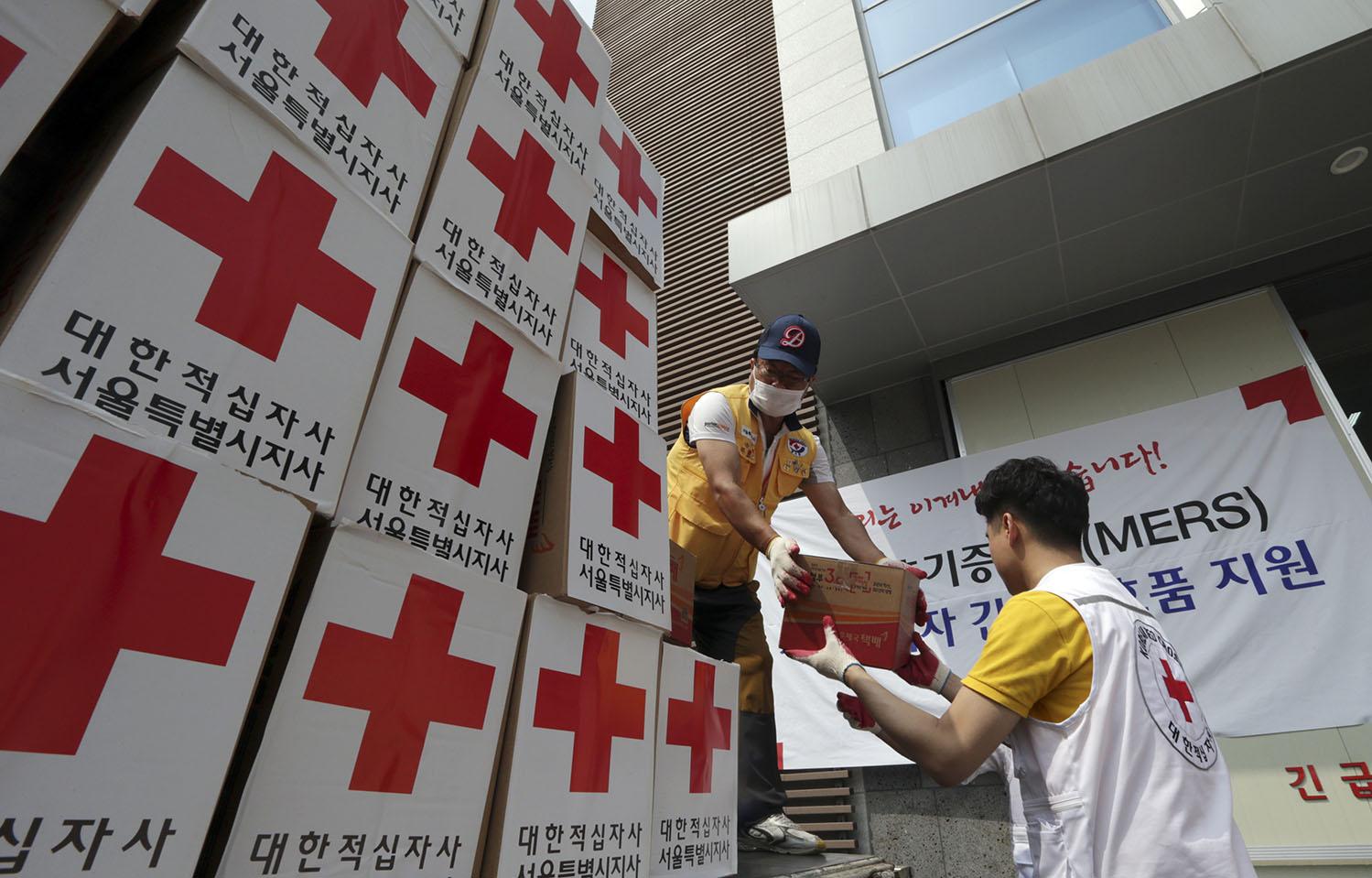 Des personnes en train de décharger des boîtes marquées d'une croix rouge (© AP Images)