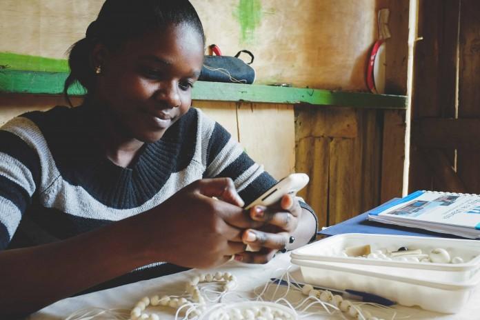Une femme utilise un téléphone portable (Crédit photo : Soko)
