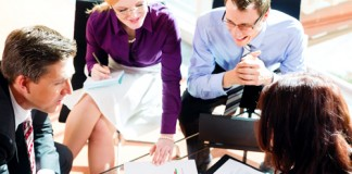 Personas sentadas, hablando y revisando documentos (Shutterstock)