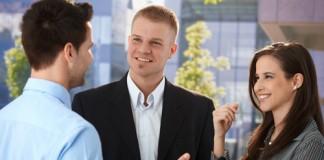 Dos hombres y una mujer hablando juntos de pie (Shutterstock)