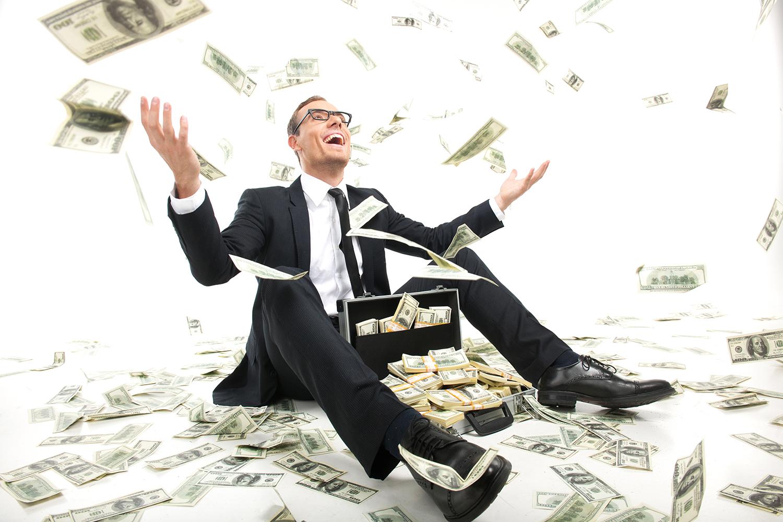Un homme d'affaires assis par terre avec, entre les jambes, un attaché-case ouvert et rempli de billets de banque, des dollars par terre et dans l'air (Shutterstock)