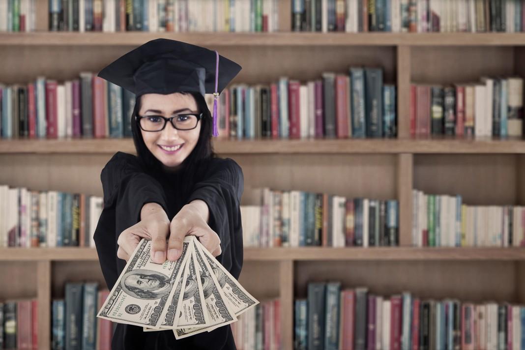 Une jeune diplômée tenant des billets de banque entre les mains, des étagères pleines de livres à l'arrière-plan (Shutterstock)