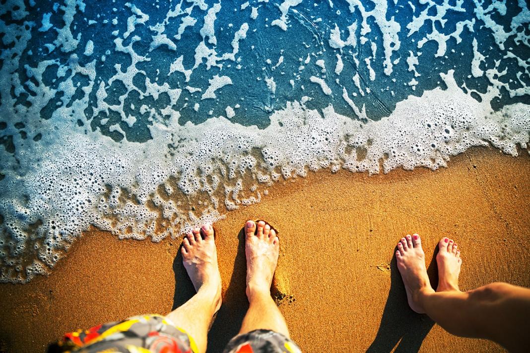 Vue de pieds sur une plage près de la mer, au bord de l'eau. (Shutterstock)