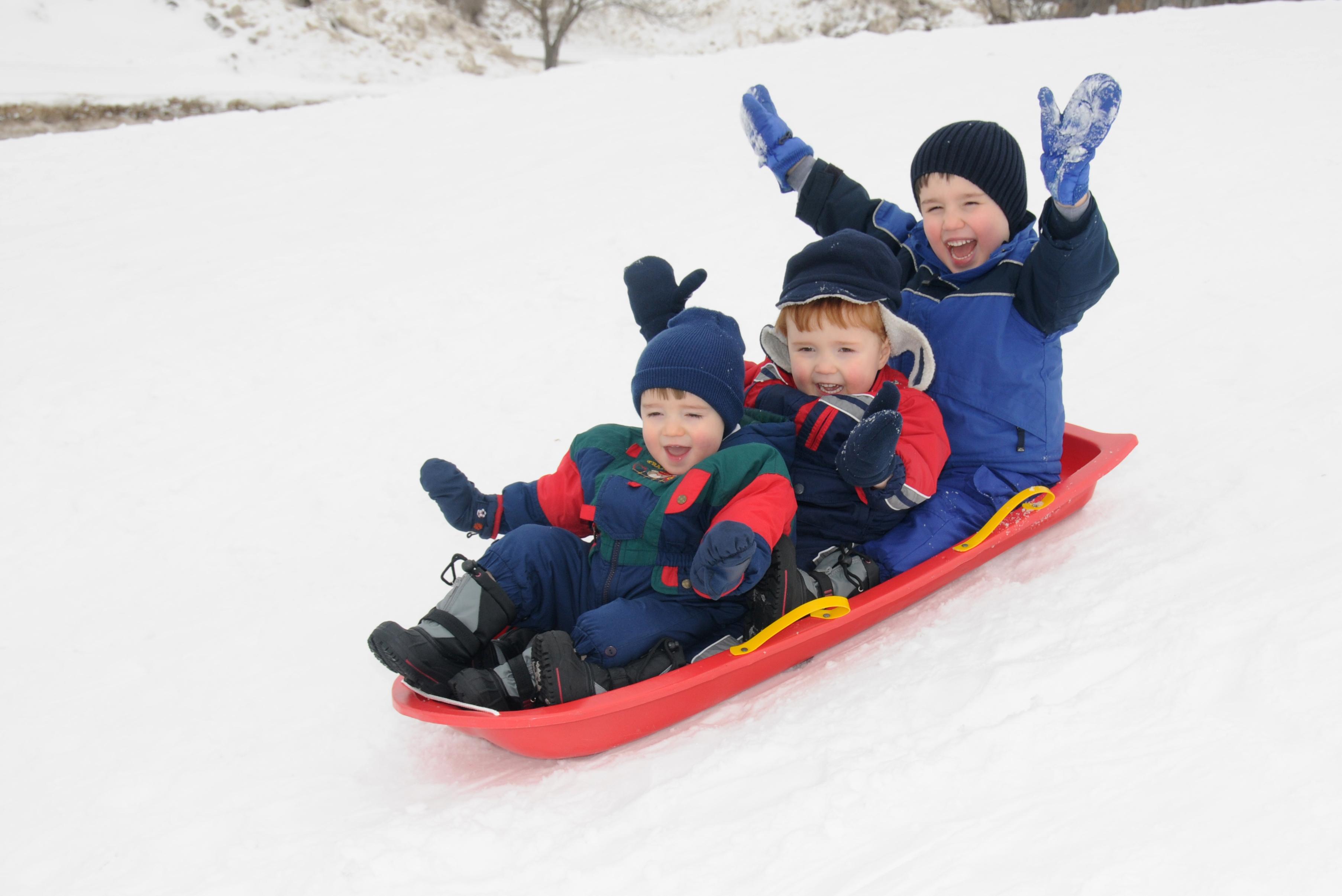 Niños montando en trineo sobre la nieve (Shutterstock)