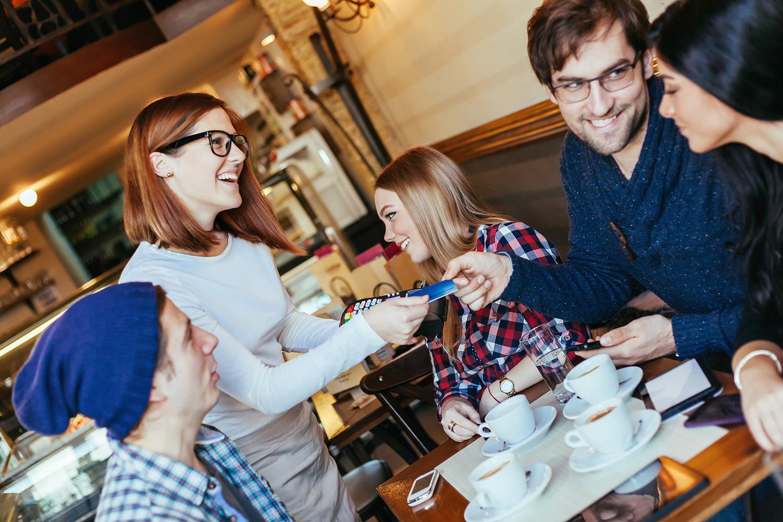 Un homme dans un restaurant, avec d'autres personnes autour de lui, en train de payer la serveuse (Shutterstock)
