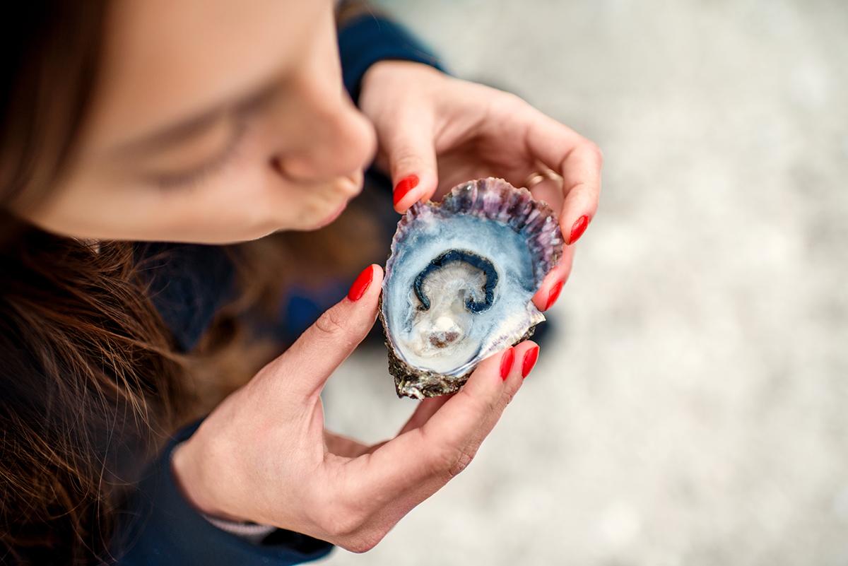 Vue d'en haut d'une femme en train de manger une huître (Shutterstock)