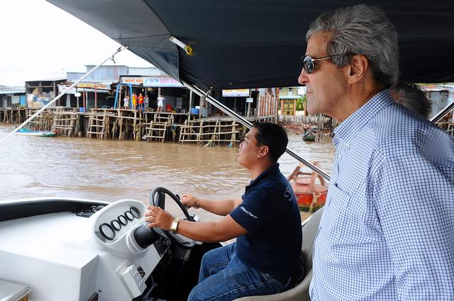 John Kerry à bord d'un bateau à moteur passant devant un village (Département d'État)