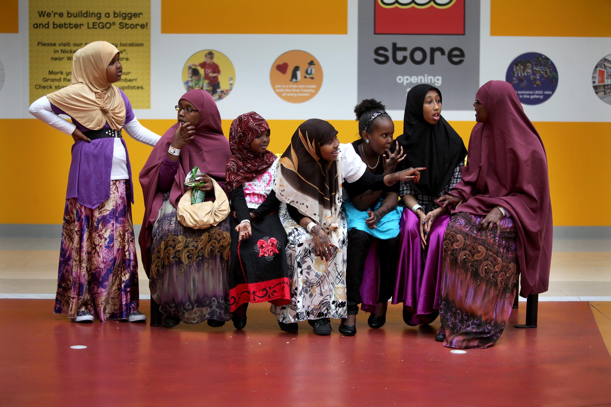 Des femmes et des filles vêtues de robes et de voiles, assises, en train de discuter. (© AP Images)