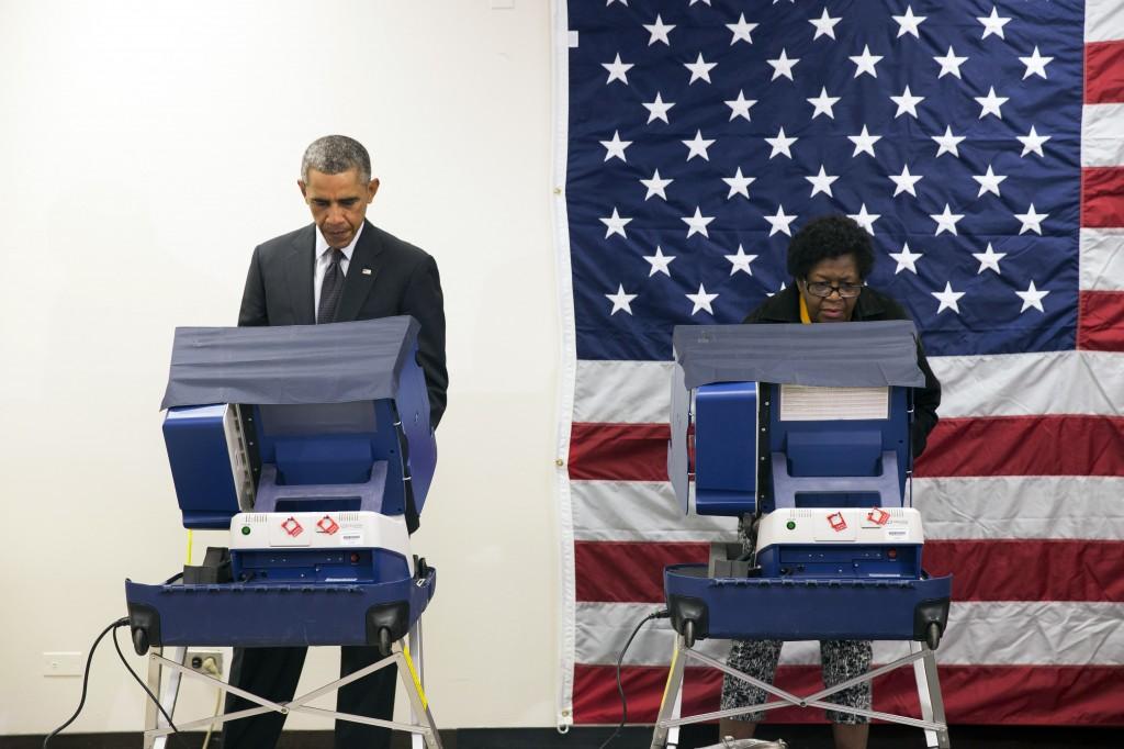 Le président Obama et une femme aux urnes ; un drapeau américain accroché au mur derrière eux (© AP Images)