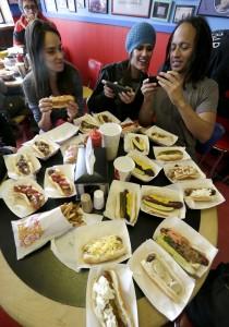 Trois jeunes femmes dans un restaurant, avec toutes sortes de hot-dogs disposés devant elles sur une table (© AP Images)