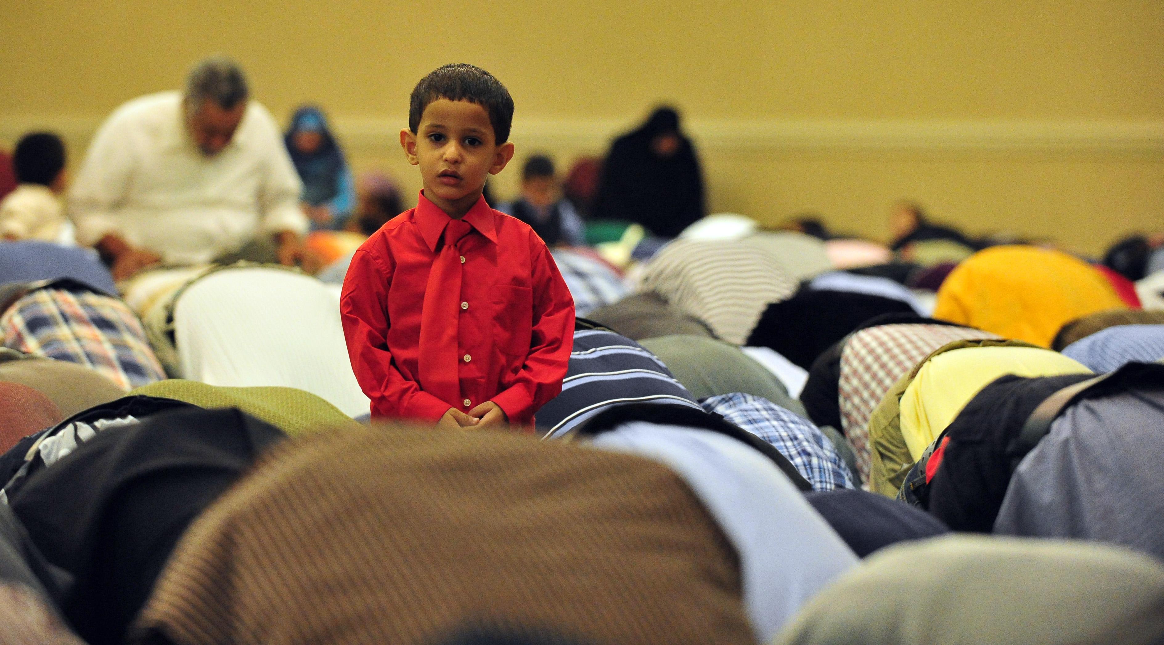 Menino com camisa e gravata vermelhas, parado entre homens ajoelhados rezando (© AP Images)