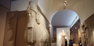 Trois hommes dans un musée qui contemplent des statues assyriennes (© AP Images)