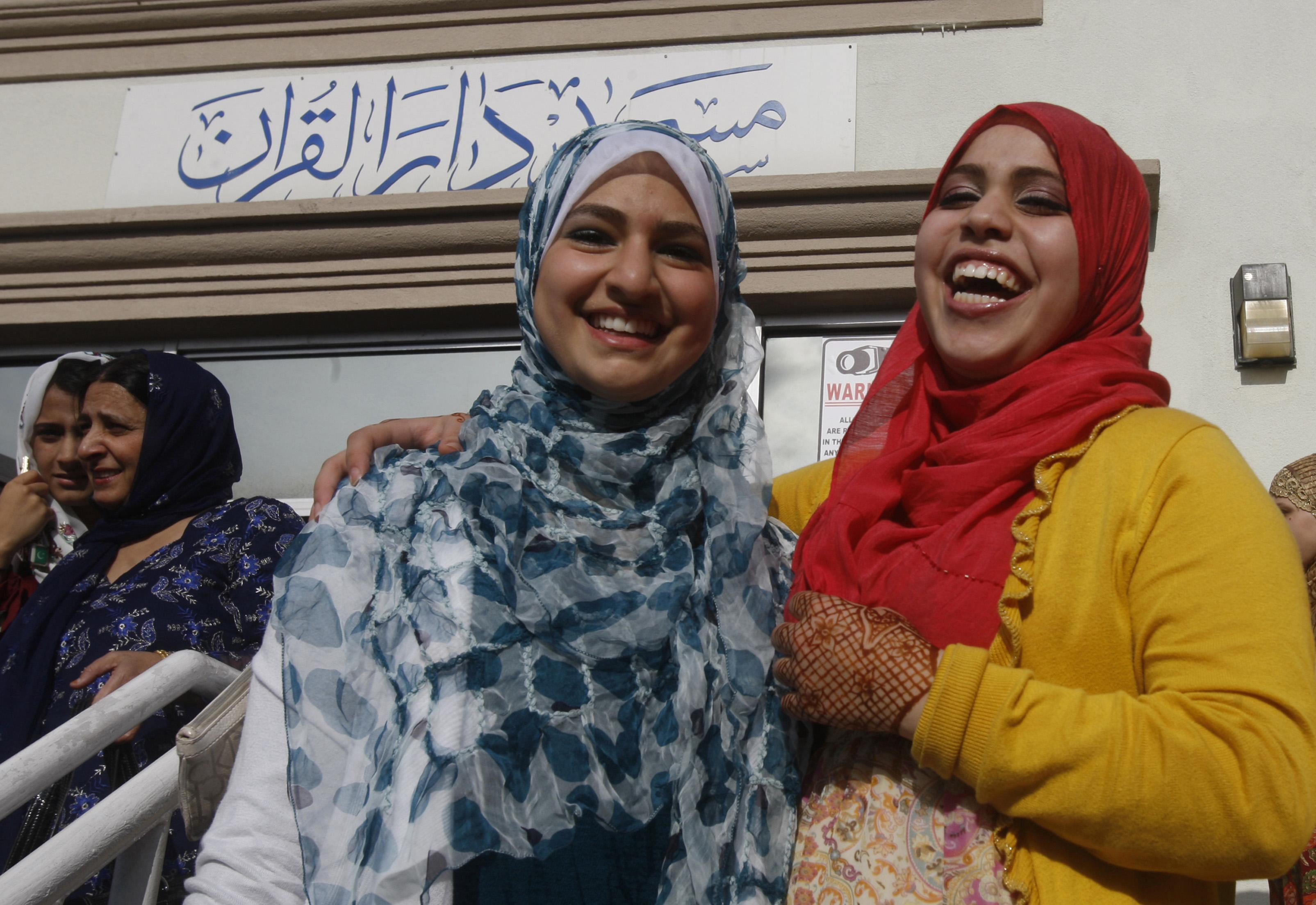 Deux femmes voilées, bras dessus, bras dessous, rient de bon cœur. (© AP Images)