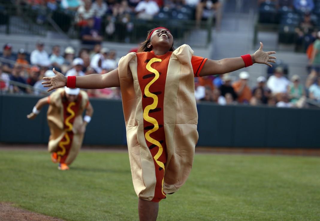 Une femme déguisée en hot-dog, souriante, la tête rejetée en arrière et les bras écartés (© AP Images)
