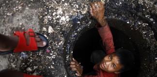 Niño saliendo de una alcantarilla (© AP Images)
