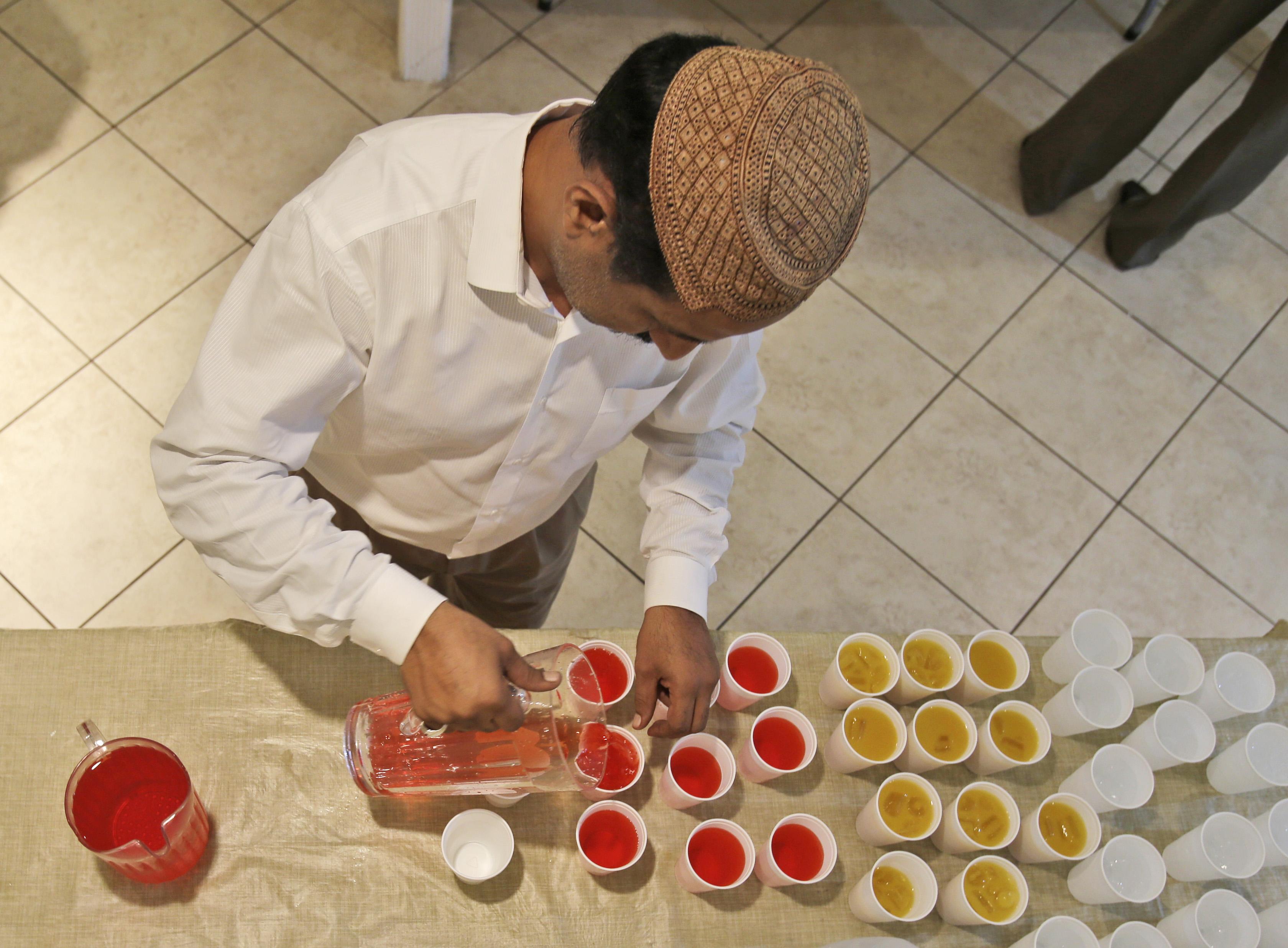 Vu du dessus, un homme coiffé d'une calotte, verse des boissons de couleur dans des verres en plastique. (© AP Images)