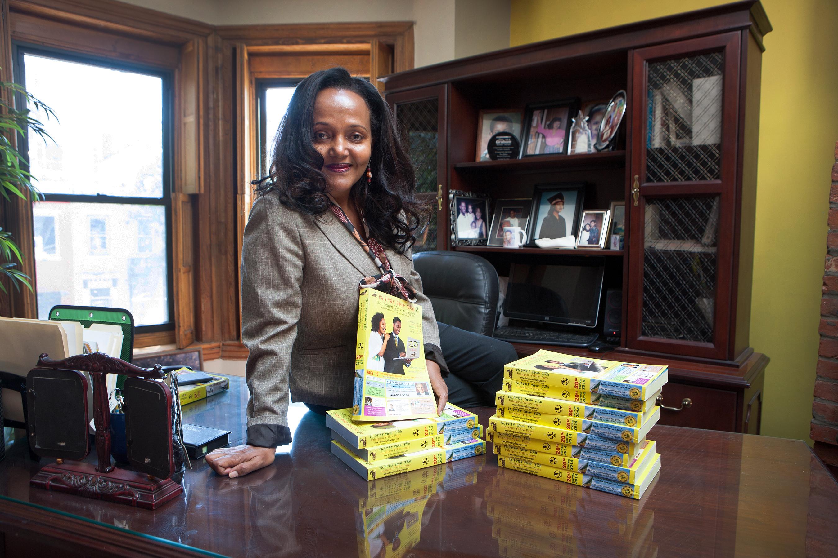Une femme assise sur un bureau et tenant un livre (David Peterson/Département d'État)