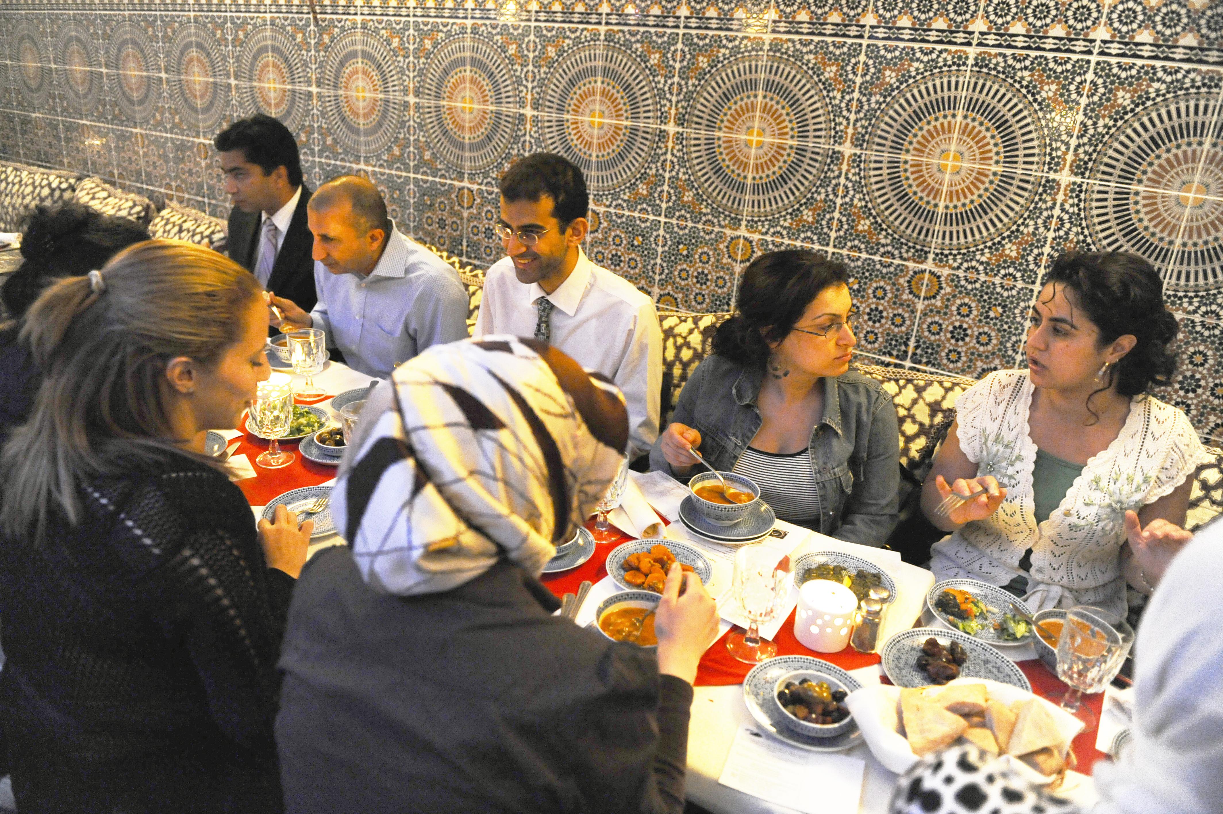 Grupo de adultos em uma longa mesa de jantar de um restaurante, com parede azulejada ao fundo (© Getty Images)