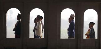 Des jeunes passent devant des fenêtres en arc. (©AP Images)