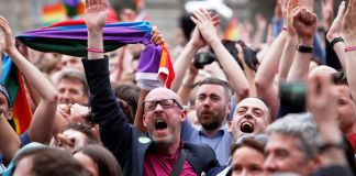 Crowd holding rainbow flags and cheering (© AP Images)