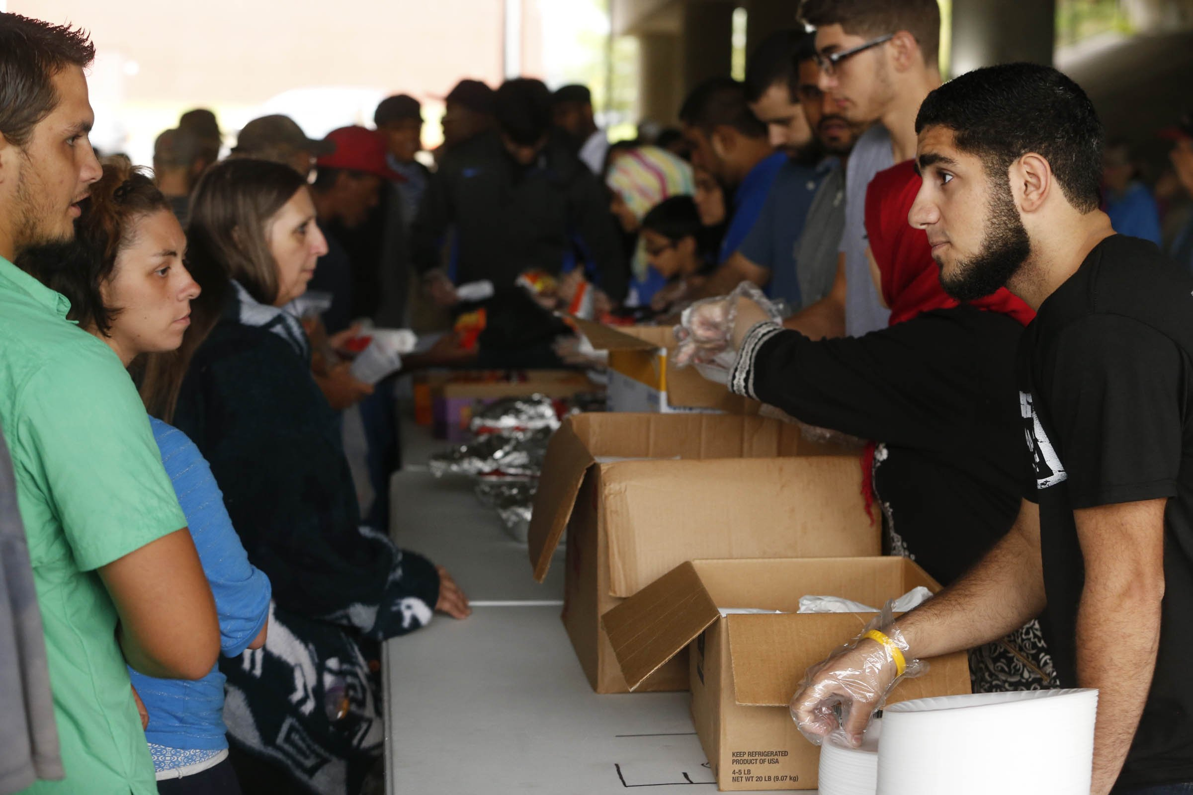 Des gens, debout derrière des tables sur lesquelles sont posés des cartons, parlent à d'autres gens qui s'avancent vers eux. (James Gibbard/Tulsa World)