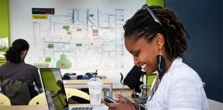 Une femme en train de taper sur un dispositif mobile devant un ordinateur portable (iHub)