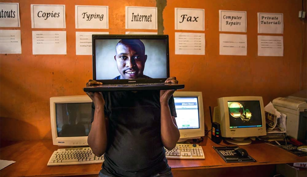 Man holding laptop with a photo of a face in front of his head (Daniel Born / The Times / Gallo Images / Getty Images)