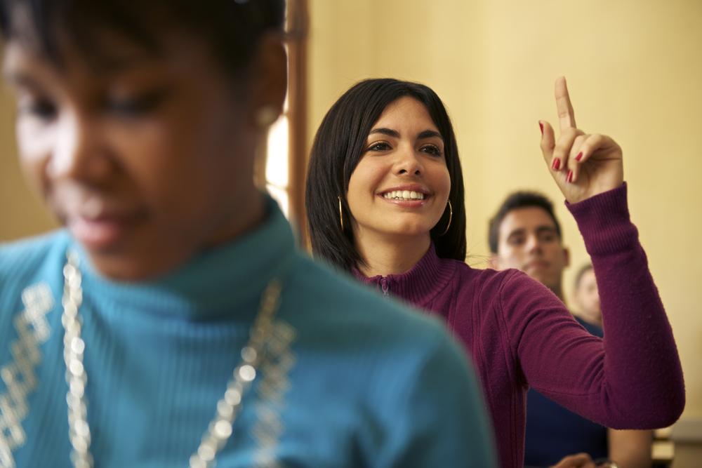 Una mujer levanta la mano en un aula (Shutterstock)