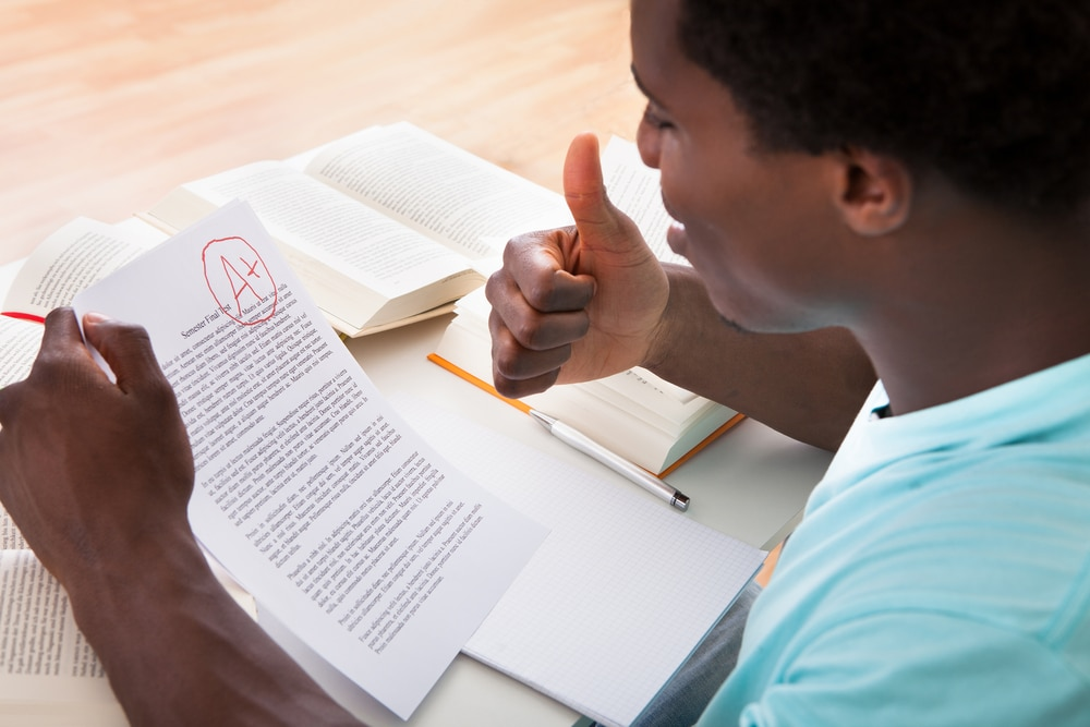Un jeune homme regarde un travail noté (Shutterstock)