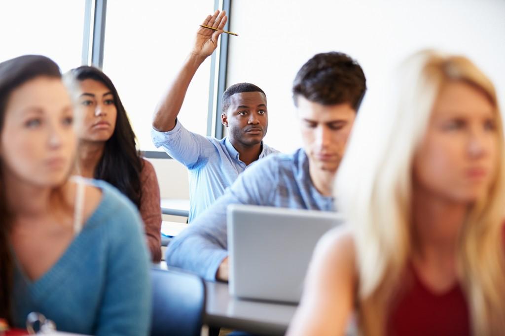 Un jeune homme levant la main pendant un cours (Shutterstock)