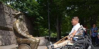 اویدوف واچیگ در حالیکه روی صندلی چرخدار به مجسمه مردی روی صندلی چرخدار نگاه می کند. (اهدایی اویدوف واچیگ)