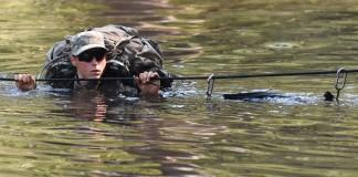 Soldado cruzando un cuerpo de agua agarrando una soga (© AP Images)