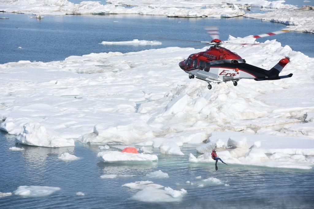 Un homme suspendu d'un hélicoptère au-dessus d'un paysage de neige et d'eau (U.S. Coast Guard/Flickr)
