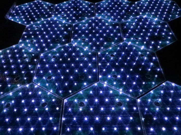 Vue de nuit d'un assemblage de dalles en verre hexagonales dans lesquelles sont intégrées des lumières LED (Crédit photo : Solar Roadways)